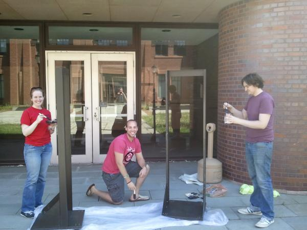Dan, Mike, and Becky repaint some electronics racks for the new space.